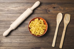 Dish with macaroni along with fork of wood and a roller on table of wood. Horizontal shoot.