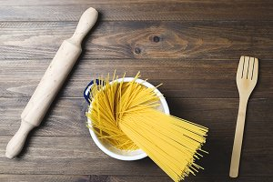 Spaghetti inside a pot next to a wooden fork on wooden table. Horizontal shoot.