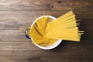 Close-up of spaghetti inside a pot on wooden table. Horizontal shoot.