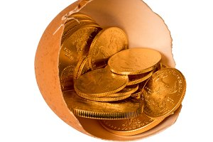Pure gold coins in egg shell illustrating savings