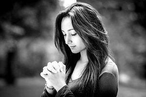 Woman hands praying in the forest.