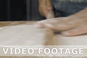 Rolling the pastry dough on a flat wooden surface