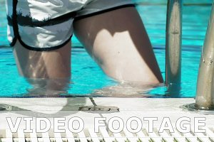 Woman going down stairs in water swimming pool
