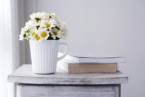 Daisy flowers in white cup