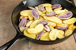 Sliced potatoes in skillet