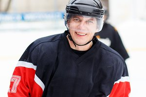 Young smiling ice hockey player in helmet and gear