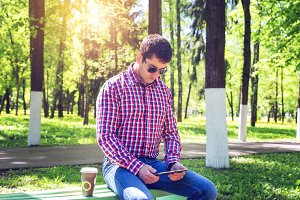 man in  shirt and jeans  sunglasses, video looks on the tablet corresponds to the social networks, in the summer  the bench, the concept of  businessman  vacation. City lifestyle.  the street in the park. Happy emotional.