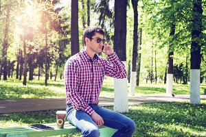 The man in the summer in the park, relaxing with a cup of coffee or tea, calling on the phone wearing glasses, jeans bright sunny day. Idea concept businessman breakfast.