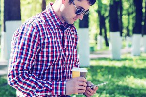 The man in the summer in the park, relaxing with a cup of coffee or tea, reading  sms on phone wearing glasses,  news feeds in social networks, in jeans bright sunny day. Idea concept businessman breakfast.