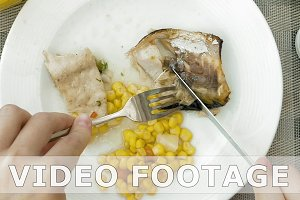 Lady is using utensils to cut meal in small bites