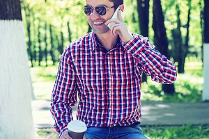 man in  shirt and jeans  glasses, talking on the phone,  smartphone, the concept of summer,  businessman  vacation. City lifestyle.  the street in the park. Happy smiling, emotional. In his hand  mug  coffee or tea.