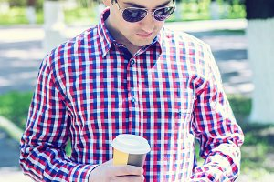 man in  shirt and jeans  sunglasses, holding  mobile phone coffee or tea, read the conversation messages on your , the concept of summer,  businessman  vacation. City lifestyle.  the street in the park