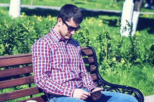 man in  shirt and jeans  sunglasses, video looks on the tablet corresponds to the social networks, in the summer  the bench, the concept of  businessman  vacation. City lifestyle.  the street in the park. Happy emotional. Next cup  coffee or tea.