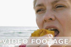 Woman enjoying delicious fruit on the summer beach
