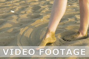 Woman is making imprints on the sand with her feet
