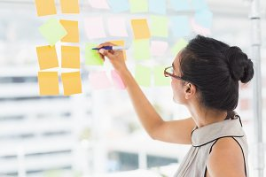 Smiling designer writing on sticky notes on window