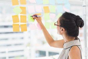 Smiling designer writing on sticky notes on window
