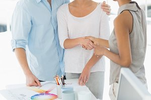 Interior designer shaking hands with smiling client