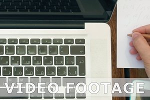 Making notes in paper notebook using a laptop pc
