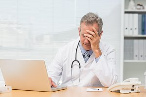 Stressed doctor sitting at his desk