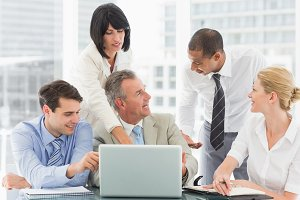 Happy business team gathered around laptop talking