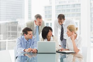 Business people gathered around laptop discussing