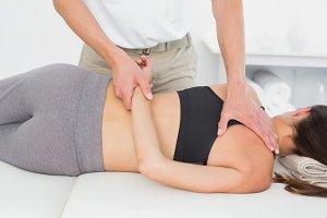 Male physiotherapist massaging womans body