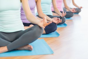 Sporty women in lotus pose at fitness studio
