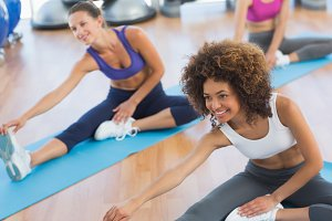 People doing stretching exercises in fitness studio
