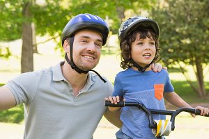 Smiling man with his son riding bicycle