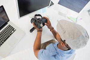 Photo editor looking at digital camera in office