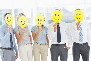 Business people holding happy smiles in front of faces