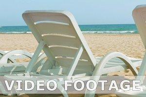 White beach chairs or beds near sea or ocean shore