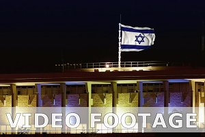 Knesset with flying waving flag of Israel at night
