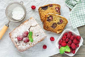 Sliced banana bread with raspberries, cherries, white chocolate, top view