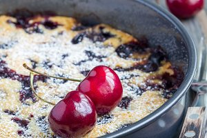 Clafoutis with cherry in baking dish, vertical