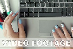 Female hands with colorful nails working on laptop