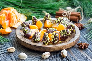 Mandarins covered with chocolate and pistachio on wooden plate