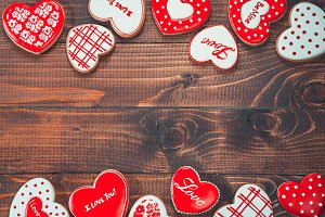 Heart-shaped biscuits for Valentine's Day. Framework with Gingerbread Valentine on wooden background