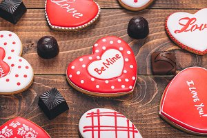 Heart-shaped biscuits for Valentine's Day. Gingerbread Valentine with chocolate on wooden background