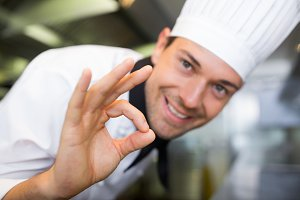 Closeup of a smiling male cook gesturing okay sign