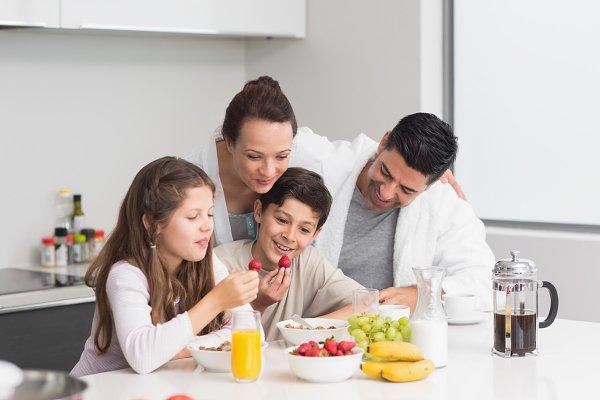 Happy kids enjoying breakfast with…