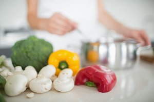 Vegetables with blurred woman preparing food in kitchen