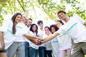 Confident environmentalists stacking hands