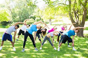 People doing stretching exercise in park