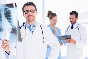 Male doctor examining xray with colleagues behind