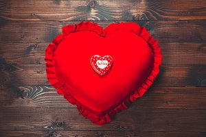 Heart-shaped biscuits on red pillow, for Valentine's Day. Gingerbread Valentine on wooden background. Free space for your text