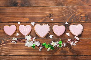 Heart-shaped biscuits and flowers for Valentine's Day. Gingerbread Valentine on wooden background. Free space for your text