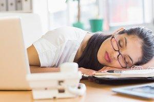 Overworked businesswoman sleeping on desk