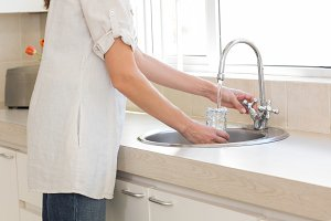 Mid section of a woman washing glass at washbasin in kitchen